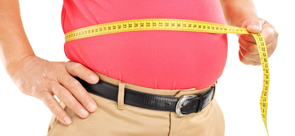 Overweight man measuring his stomach