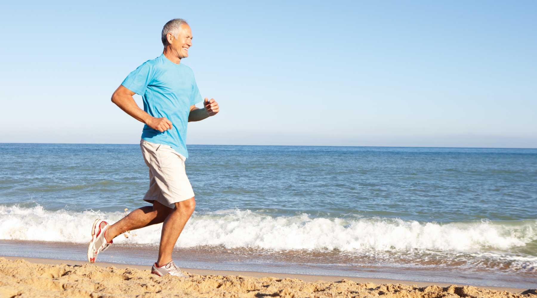 Older man running along the beach